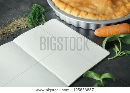 Open notebook and tasty turkey pot pie with ingredients on gray background