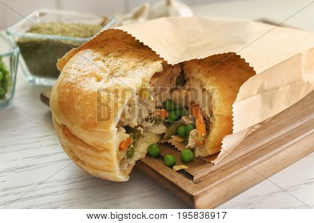 Paper bag with tasty turkey pot pie on white wooden table, closeup