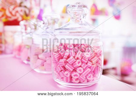 Different candies in jars at shop