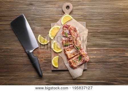 Raw pork ribs and meat cleaver knife on wooden background