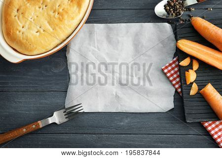 Composition with piece of parchment and tasty turkey pot pie on wooden background