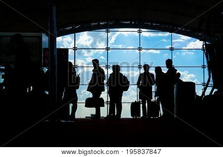 Silhouettes of people waiting for their flight at the airport