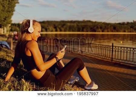 Girl runner sitting in the park listening to music on headphones with phone.