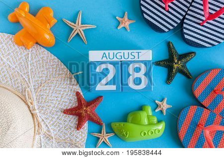 August 28th. Image of August 28 calendar with summer beach accessories and traveler outfit on background. Summer day, Vacation concept.