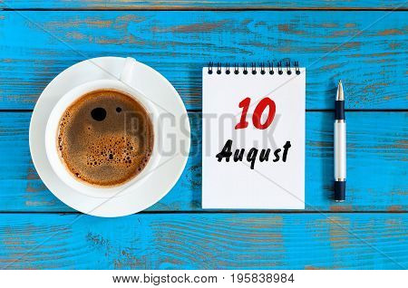 August 10th. Day 10 of month, loose-leaf calendar on blue background with morning coffee cup. Summer time. Unique top view.