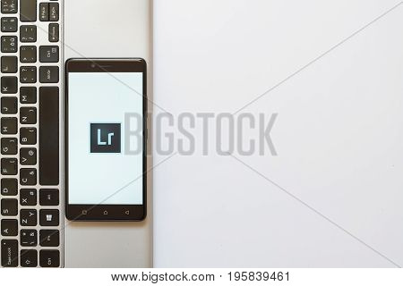 Los Angeles, USA, july 18, 2017: Adobe photoshop lightroom logo on smartphone screen placed on the laptop on white background.