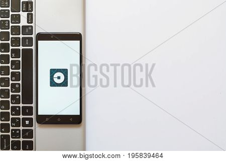 Los Angeles, USA, july 18, 2017: Uber logo on smartphone screen placed on the laptop on white background.