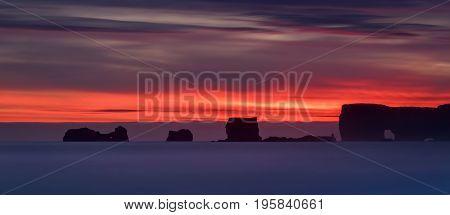 Rocks of Dyrholaey peninsula in colorful sunset Iceland