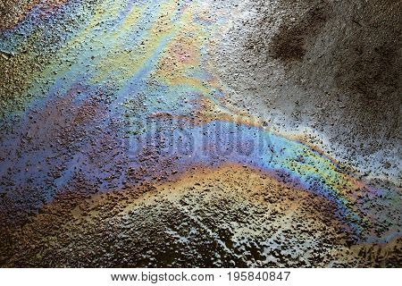 Background texture of an oil spill on road. Environmental pollution