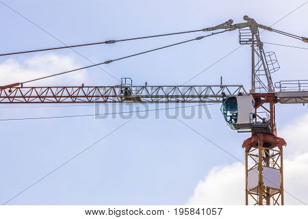 Construction tower crane cabin in the blue sky and clouds