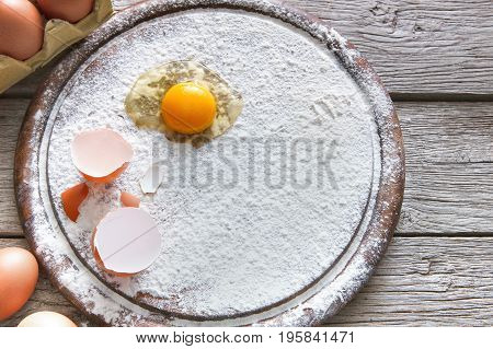 Baking concept. Flour and eggs on wooden cutting board, cooking ingredients. Prepare for making yeast dough. Copy space on wood