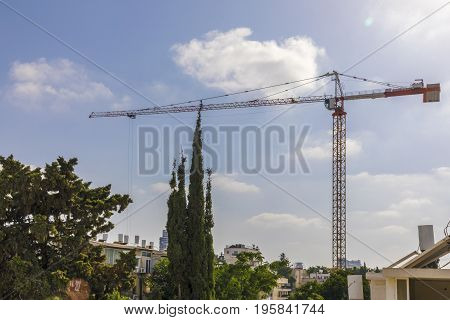 Construction crane with cables down in a dense neighborhood with green trees blue sky and strong sun light