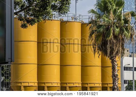 Yellow cement silos standing in line with corporate building on background and green trees