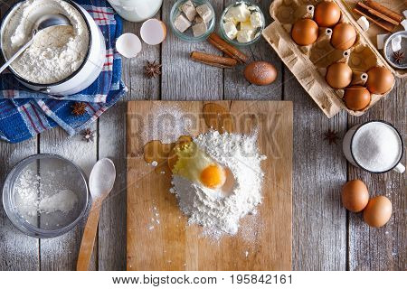 Baking concept. Flour and egg yolk on board on rustic wooden table with ingredients for pastry. Making sweet yeast dough, top view