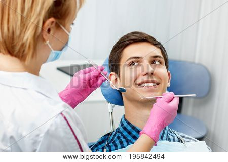 Handsome young man is having dental check up in dental office. Dentist is examining a patient teeth with dental tools. Dentistry