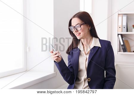 Communication, technology, success. Business woman using mobile phone near window at office workplace, copy space