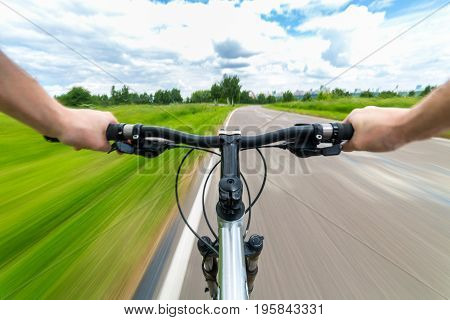 Rider driving bicycle on an asphalt road. Two hand on bike handlebar. Motion blurred background