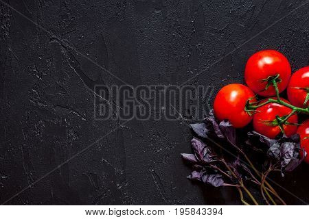 Cook workplace. Tomato on black table background top view.