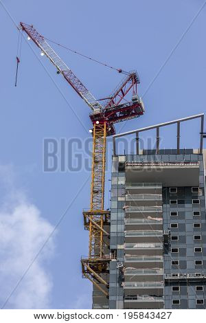 Multistory residential building with balconies under construction with scaffolds and crane on side cloudy sky