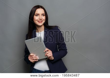 Elegant business woman in formal suit standing with tablet on gray studio background, smiling at camera, copy space