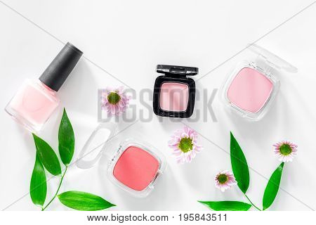 Cosmetics. Blush, eyeshadow and nail polish on white table background top view.
