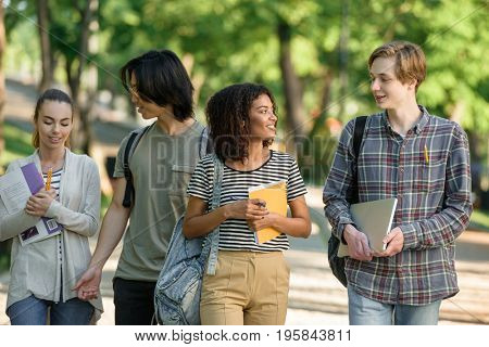 Picture of multiethnic group of smiling young students walking outdoors. Looking aside.