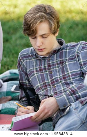 Image of young student boy sitting studying outdoors. Looking aside.