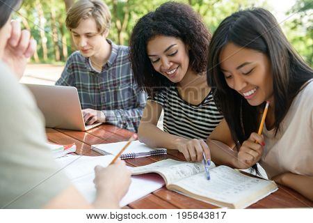 Image of multiethnic group of cheerful young students sitting and studying outdoors while using laptop. Looking aside.