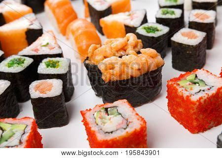 Traditional japanese food restaurant delivery. Closeup of sushi set. California and vegetarian rolls, gunkan with shrimps and salmon sashimi at white background