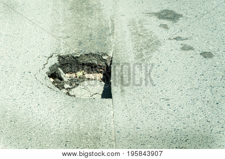 Dangerous hole on the asphalt roadway. Road damage.
