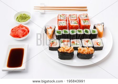 Japanese food restaurant, colorful rolls, gunkan and sushi platter. Set with chopsticks, ginger, wasabi and soy sauce. Pov, isolated on white background