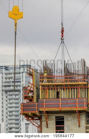 Construction worker wearing yellow hard hat and safety vest secure the crane chain on scaffold with residential building on background vertical