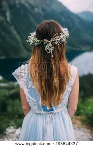 the bride in a beautiful blue dress with a deep neckline at the back with a wreath on her head of white flowers stands on a background of mountains and lakes