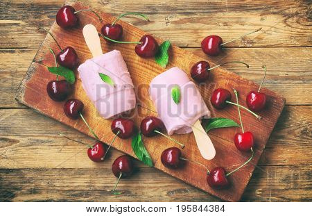 Homemade yogurt ice cream with cherry popsicle on stick on wooden board on table mint leaves top view