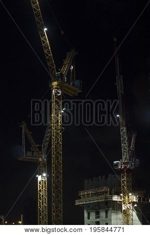 Construction site with three lighted cranes at night vertical