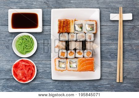Japanese food restaurant delivery - sushi maki, unagi and roll platter set isolated on blue wood background, above view