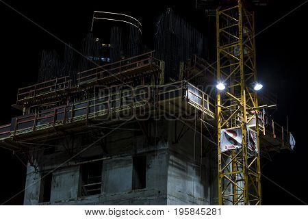 Building under construction stories with yellow crane mast attached on the side lighted by spotlight at night