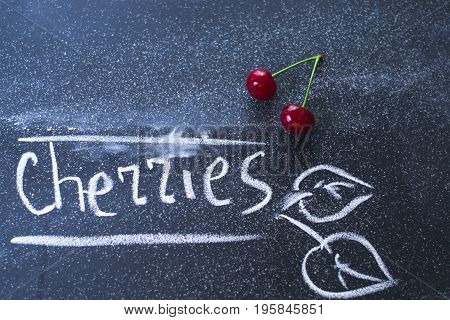 Cherries on a black matte background with chalk text