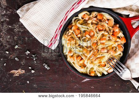 Homemade pasta or noodles with fried salmon fish and pine nuts in cream sauce in a pan on a wooden table, selective focus