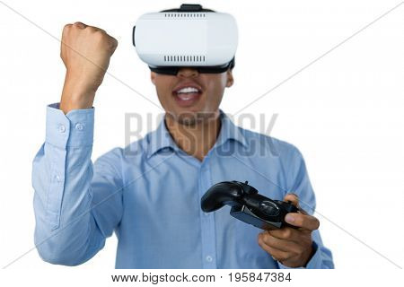 Businessman with vr glasses clenching fist while playing video game against white background