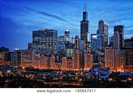 Chicago lakefront skyline cityscape at night by millennium park with a dramatic cloudy sky.