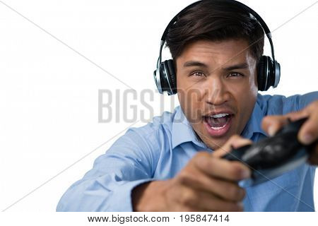 Young businessman making face while playing video game against white background