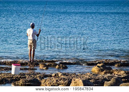 one man the fisherman costs on the stone coast and catches a rod fish in the sea
