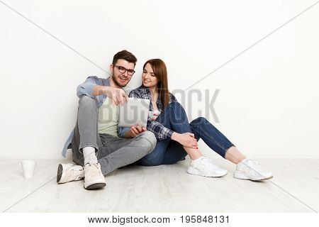Wasting money for shopping. Couple at home sitting on floor and using digital gadget and drinking coffee together, white background