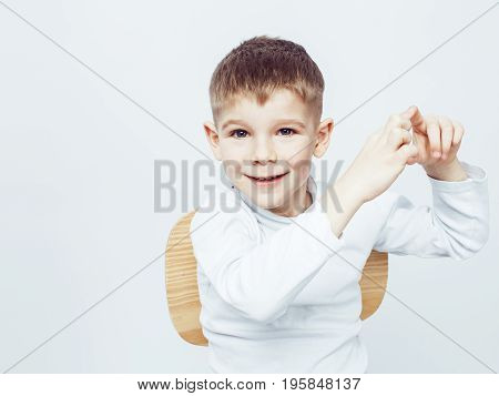 young pretty little cute boy kid wondering, posing emotional face isolated on white background, gesture happy smiling close up, lifestyle real people concept modern