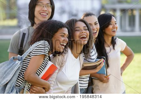 Image of multiethnic group of young smiling students standing outdoors.