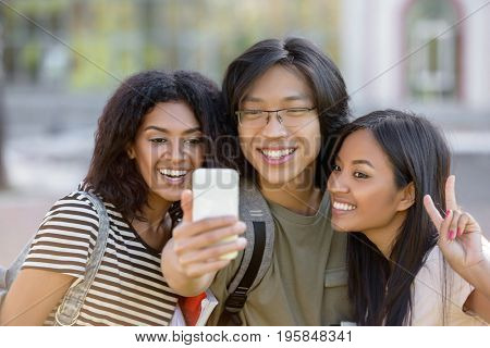 Image of multiethnic group of young happy students standing outdoors make selfie by phone. Looking aside.