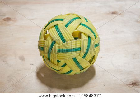 Green and yellow rattan ball on wooden floor. Selective focus.