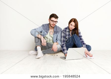 Couple planning design project for apartment, sitting on floor with laptop on white background at new home