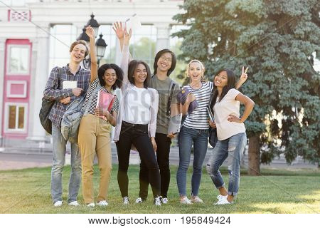 Picture of multiethnic group of young cheerful students standing outdoors waving. Looking at camera.